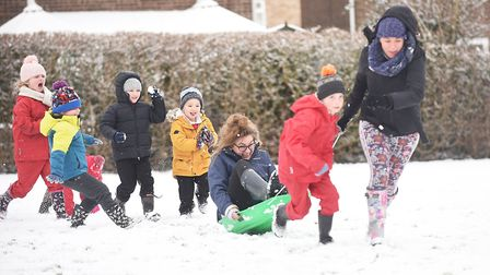 South Wootton Infant School reception teacher Emily Riddington being pulled along on a sledge by Rac