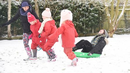 Sarah Newman being pulled along on a sledge by pupils at South Wootton Infant School. Picture: Ian B