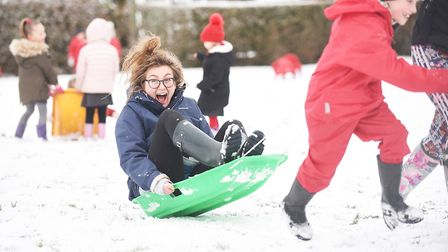 South Wootton Infant School reception teacher Emily Riddington being pulled along on a sledge by pup