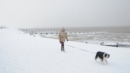A woman walks her dog along the snow-covered Prom at Hunstanton. Picture: Chris Bishop