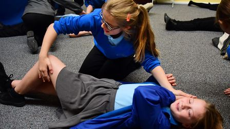 George White Junior School children learn the recovery position from the St John Ambulance during a