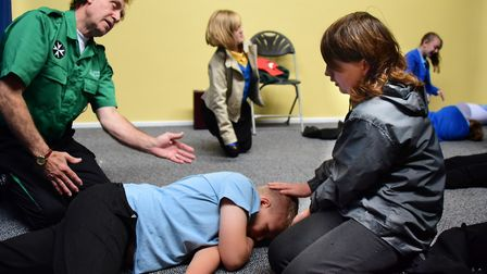 George White Junior School children learn the recovery position from Kennie Harkin-Perry of the St J