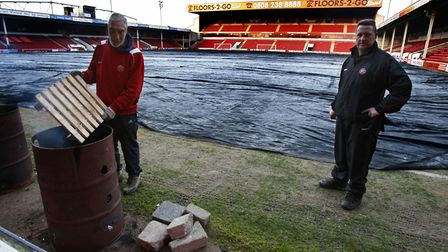 Groundstaff at Walsall re-cover the pitch after the game against City in December, 2009, was called