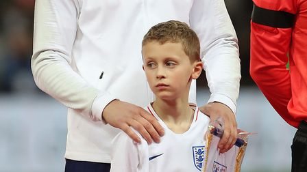 England's Eric Dier stands with mascot Ethan Thomas, son of Simon Thomas before the international fr