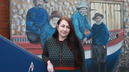 Sheringham Museum manager Lisa Little in front of a mural painted by local artist Colin Seal on the