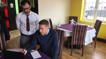 EDP reporter Luke Powell and a member of staff at Rishi retaurant picking the March community hero.