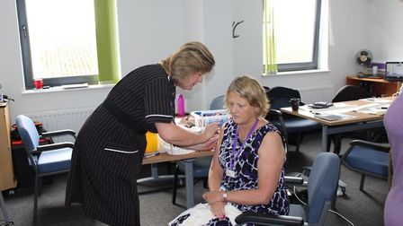 Assistant Director of Infection Prevention & Control Teresa Lewis administering a flu jab to Directo