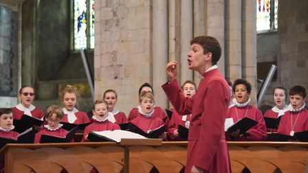 The master of music, Ashley Grote, conducts the Norwich Cathedral choir as the Cathedral music appea