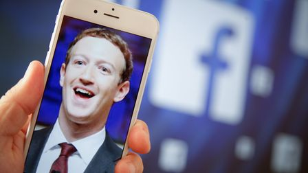 A portrait of Facebook found Mark Zuckerberg is seen on an iPhone in this photo illustration on 28 A