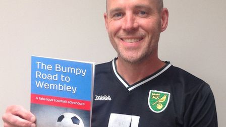 """Peter Barnes with his children's fiction book """"The Bumpy Road to Wembley"""""""