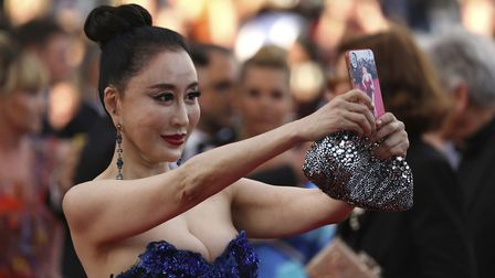 A guest takes a selfie photograph upon arrival at the opening ceremony of the 71st international fil