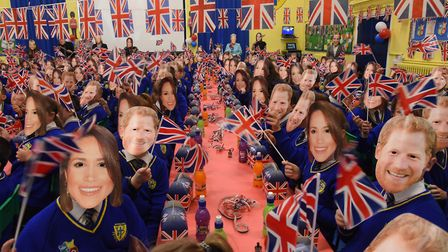 Howard Primary School children at King's Lynn wear Meghan and Harry masks as the school holds a mass