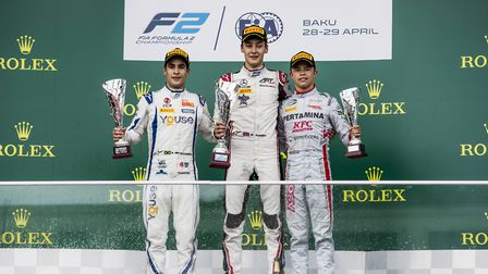 George Russell standing proudly on top of the FIA Formula Two race two podium with Sergio Sette Cama