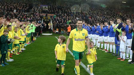 Wes Hoolahan of Norwich takes to the pitch with his children as the players from both sides form a g