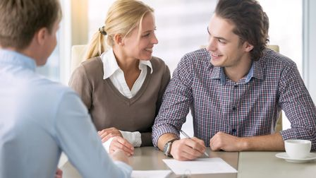 A young couple meeting their bank manager. Bank / mortgage / loans / credit / debt / money / house b