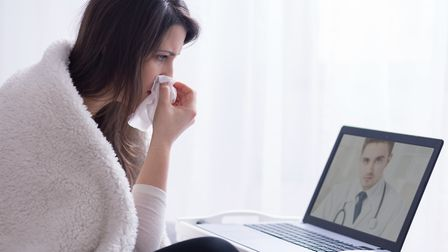 Woman holding hanky during online consultation with doctor. Photo: Getty Images