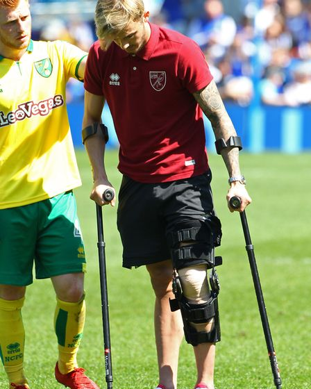 James Maddison of Norwich on crutches waves to the the traveling Norwich fans at the end of the Sky