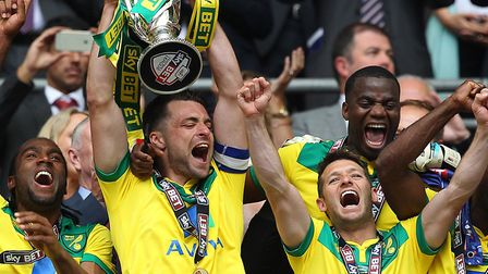 Russell Martin lifts the play-off trophy, flanked by Wes Hoolahan. Picture: Paul Chesterton/Focus Im