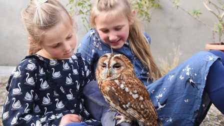 Lana Townshend, left, and her sister, Eva, with one-year-old Arthur, one of a pair of tawny owls kep