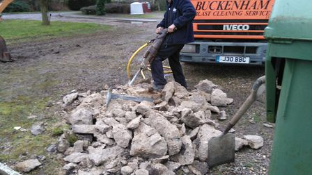 Stephen Warner who has almost finished breaking a piece of concrete from under one of the old pieces