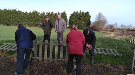 Volunteers digging down to remove of the fence panels at the Ringsfield and Weston Play Area Picture