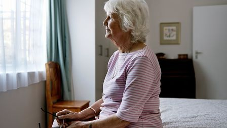 An elderly woman sitting on her bed dealing with depression. Photo: Getty Images/iStockphoto