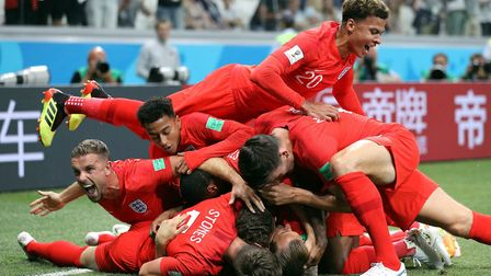 England's Harry Kane (hidden) is mobbed by team-mates as he scores his side's first goal of the game