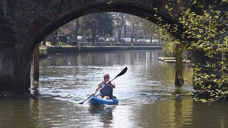 A kayaker goes under Bishop Bridge in the sunshine on the River Wensum. Picture: DENISE BRADLEY