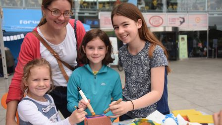 Sisters, Lucy, five, Charlotte, eight, and Alice Platten, 11, with mum Esther, paint a bee box at th