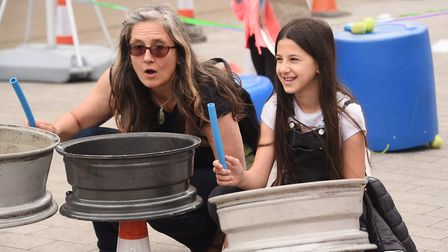Playing car wheels in the Junk Orchestra at the One Planet Festival. Picture: DENISE BRADLEY