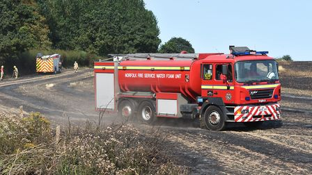 Firefighters tackle a field fire just off the A140 roundabout near Norwich Airport.Byline: Sonya Dun