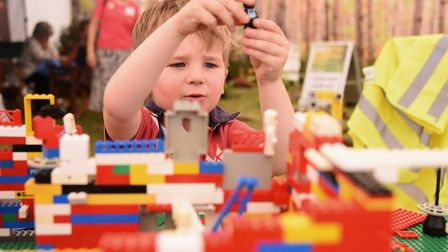 Four-year-old Oliver Brown plays with the Lego church being built at the Diocese of Norwich stand at