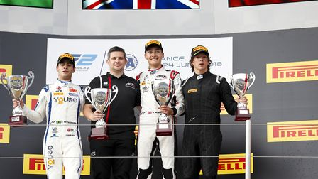 George Russell standing on top of the FIA Formula Two race one podium at the Paul Ricard Circuit in