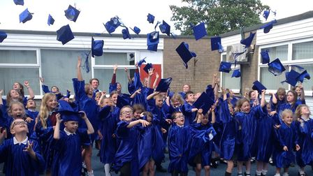 Children celebrate by throwing their mortar board hats in the air PHOTO: Toftwood Infant School