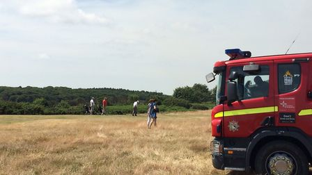 Fire on cliff near Cromer lighthouse. But you can't interrupt a game of golf - see them playing near