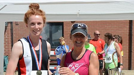 Alicia Lacey picks up the winner's trophy after breaking the course record at the Harling 10K. Pictu