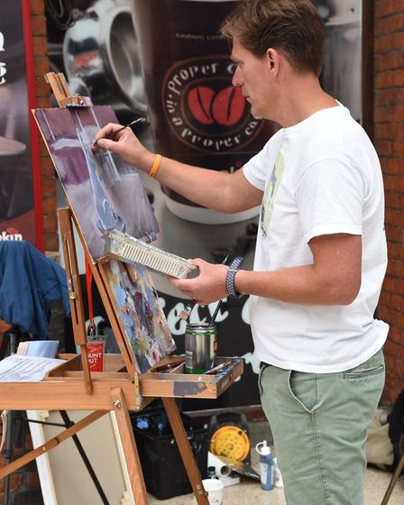 Tom Cringle painting a canvas of his hare at Norwich Railway Station. Byline: Sonya DuncanCopyright: