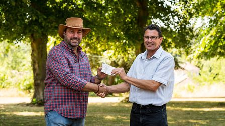 Gordon Bush (right) presents a 1,000 cheque towards the cost of a multi-use games area to NSFT Chief