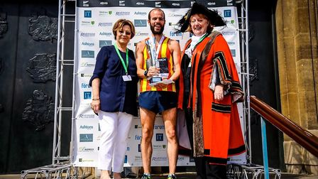 Nick Earl picks up the Run Norwich winner's trophy in 2016 from Delia Smith, who started the race. P