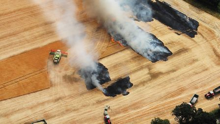 Farmers battle to save the rest of the crop after a fileld fire at Blofield in July. Picture: Mike P