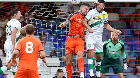 New Norwich City captain Grant Hanley wins a header in the friendly win at Luton Town, watched by ne