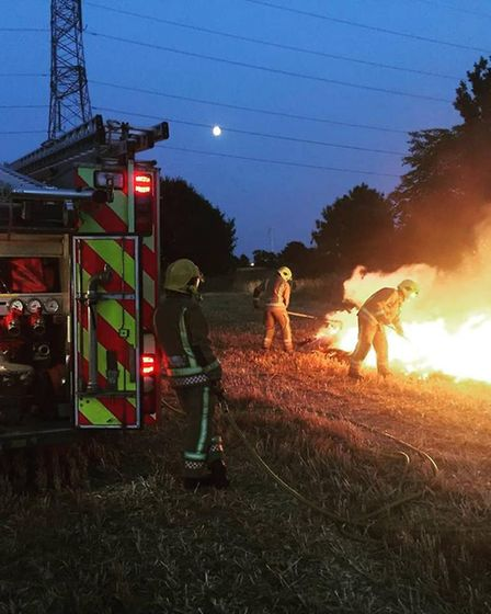 Fire fighters put out a straw bale fire in Thrandeston. PHOTO: Norfolk Fire and Rescue Service