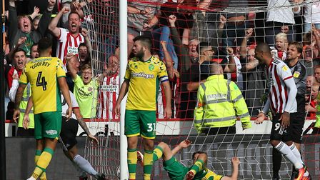 The Norwich players look dejected as Billy Sharp of Sheffield United celebrates scoring his sides 2n