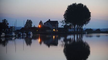 The still water of the River Yare in the evening at the Beauchamp Arms at Buckenham. Picture: Denise