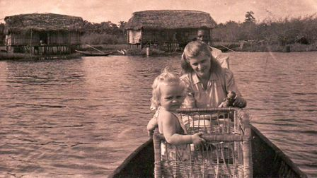 In Nigeria with her daughter Sarah in the basket on the canoe. Photo: Kingsley Healthcare