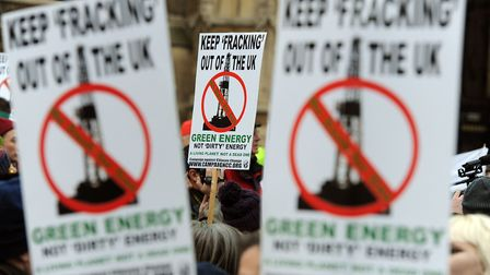 """Demonstrators hold placards as they erected a seven meter high """"fracking rig"""" calling for a ban on e"""