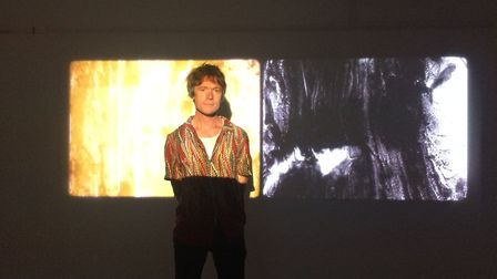 Julian Hand stands in front of his film Erosion at the NUA MA Show. PHOTO: Sophie Smith