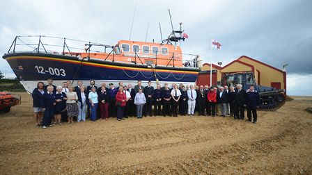 Members of Wells Lifeboat crew and guests standing in front of the station's current all-weather lif