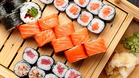 Sushi set on a wooden plate and dark concrete background. Picture: Getty Images/iStockphoto