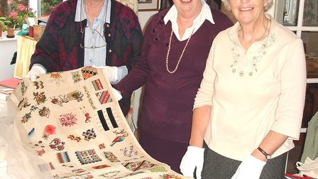 From left, Jane Peaster, Rosemary Jewers and Norah Tuck with the needlework sampler, which will go